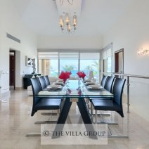 Dining area featuring an elegant glass table with 8 leather chairs