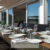 Outdoor dining over looking the pool and with sea views