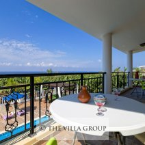 Small table and chairs on the balcony overlooking the pool and with sea views